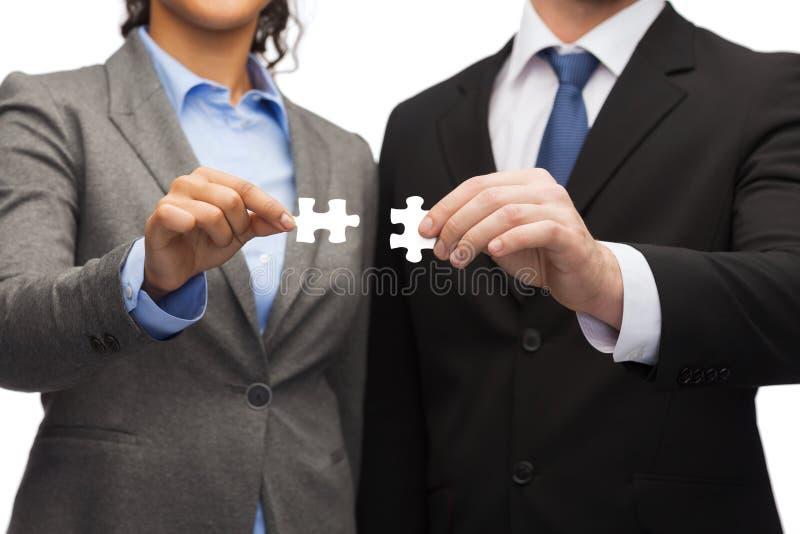 Homem de negócios e mulher de negócios com partes do enigma foto de stock royalty free