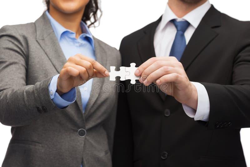 Homem de negócios e mulher de negócios com partes do enigma fotografia de stock royalty free