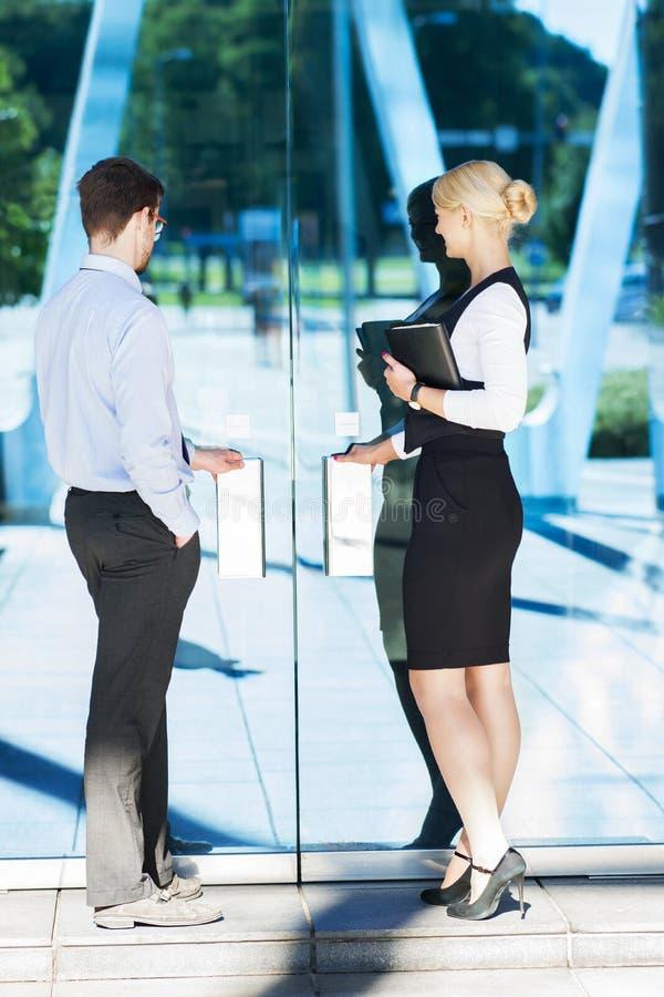 Homem de negócios e mulher de negócios no formalwear que está perto da entrada do hotel na véspera da reunião imagens de stock