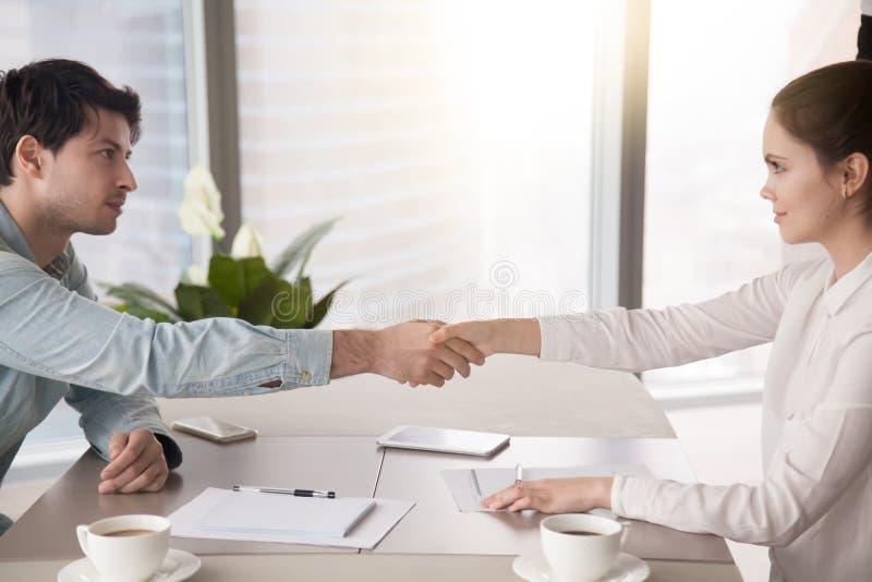 Homem de negócios e mulher de negócios que agitam as mãos Acordo do negócio imagens de stock