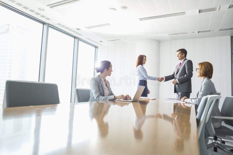 Homem de negócios e mulher de negócios que agitam as mãos na sala de conferências imagem de stock