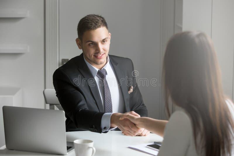 Homem de negócios e mulher de negócios que agitam as mãos no acordo imagem de stock royalty free