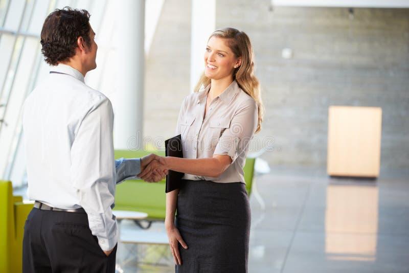 Homem de negócios e mulher de negócios que agitam as mãos no escritório foto de stock