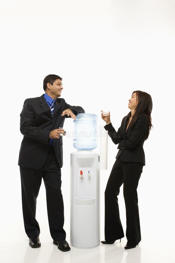 Homem de negócios e mulher de negócios que estão no refrigerador de água. imagem de stock royalty free