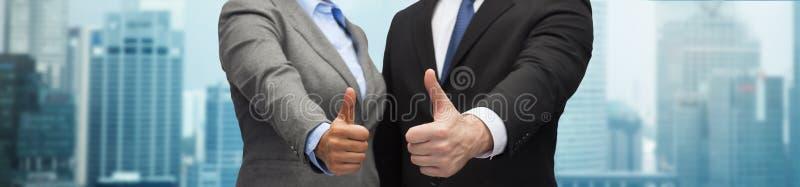 Homem de negócios e mulher de negócios que mostram os polegares acima imagens de stock royalty free