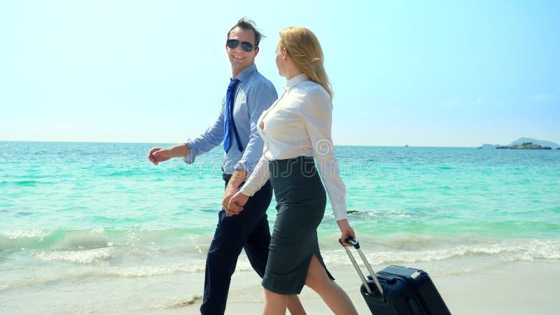 Homem de negócios e mulher de negócio com uma mala de viagem que anda ao longo da praia branca da areia na ilha foto de stock royalty free