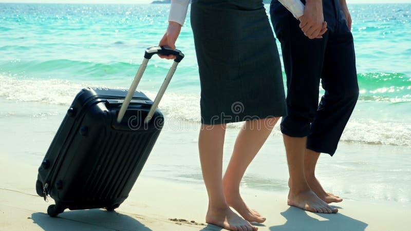 Homem de negócios e mulher de negócio com uma mala de viagem que anda ao longo da praia branca da areia na ilha fotografia de stock