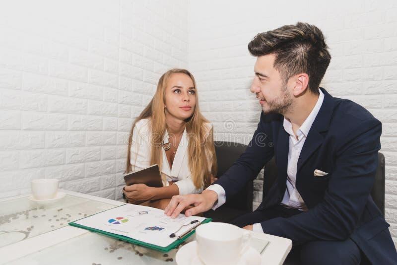 Homem de negócios e mulher de negócio que analisa cartas e gráfico da renda foto de stock