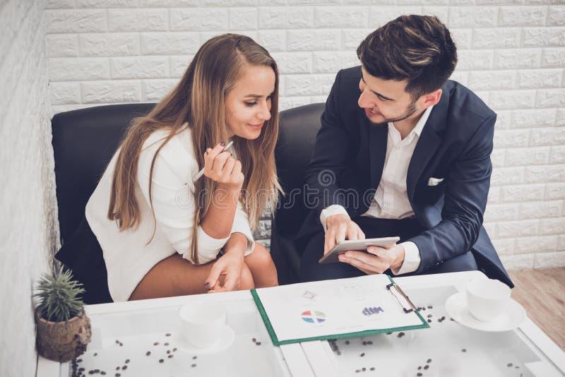 Homem de negócios e mulher de negócio que analisa cartas e gráfico da renda imagens de stock