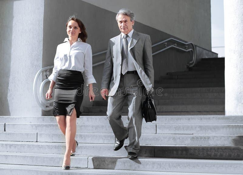 Homem de negócios e mulher de negócio que anda abaixo das escadas abertas do prédio de escritórios imagem de stock