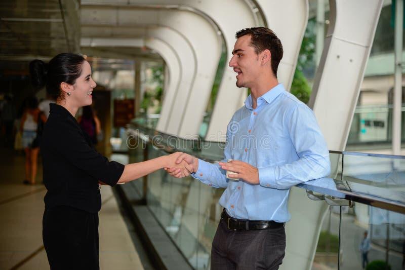 Homem de negócios e mulher de negócios que agitam as mãos para o acordo e a conversa do sucesso sobre o negócio imagens de stock