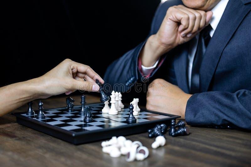 Homem de negócios e mulher de negócios que jogam a xadrez e que pensam sobre s imagem de stock