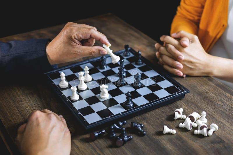 Homem de negócios e mulher de negócios que jogam a xadrez e que pensam sobre s imagens de stock