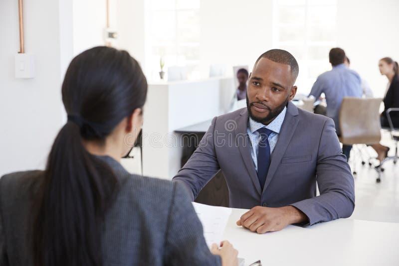 Homem de negócios e mulher que sentam-se na mesa em um escritório de plano aberto fotos de stock