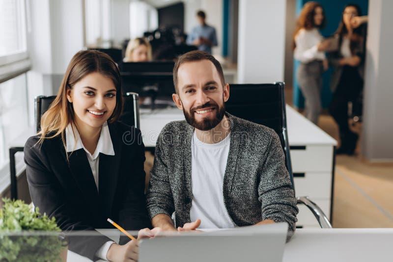 Homem de negócios e mulher de negócios que trabalham com o portátil no escritório moderno imagem de stock royalty free