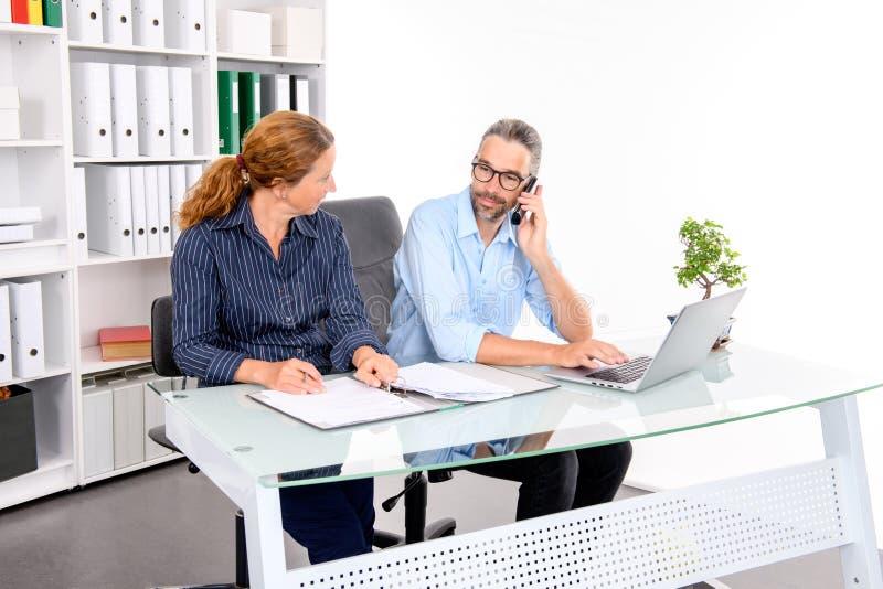 Homem de negócios e mulher de negócios que trabalham junto no escritório imagem de stock royalty free