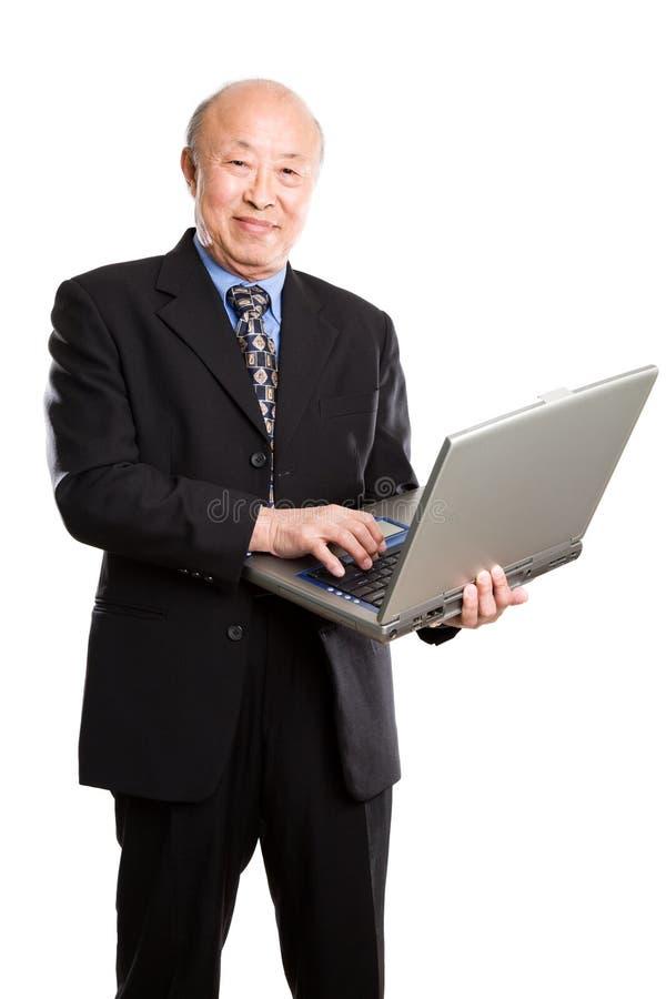 Homem de negócios e portátil asiáticos sênior imagem de stock royalty free