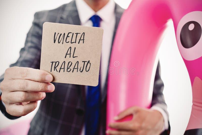 Homem de negócios e texto de volta ao trabalho no espanhol foto de stock