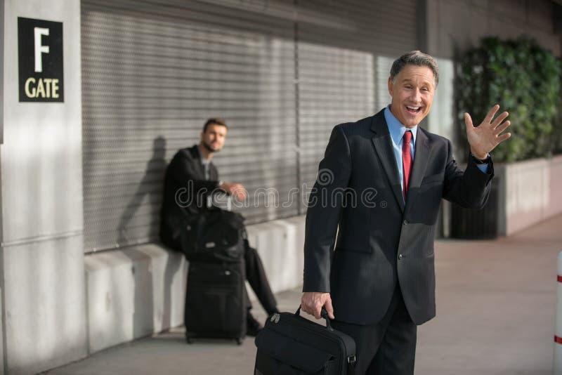 Homem de negócios ectático de sorriso At Aiport Gate fotografia de stock royalty free