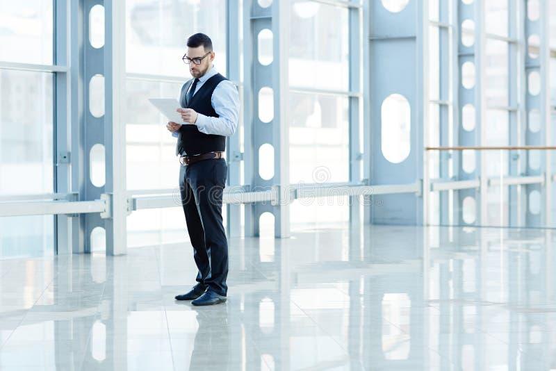 Homem de negócios elegante Reading Documents no salão de vidro moderno fotos de stock royalty free