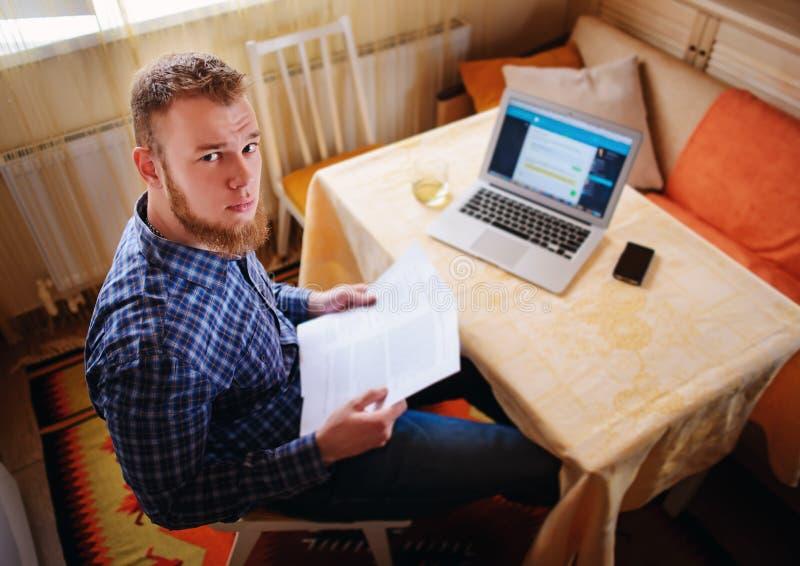 Homem de negócios em casa, está trabalhando com um portátil, verificando o documento e as contas, olhando a câmera imagem de stock royalty free