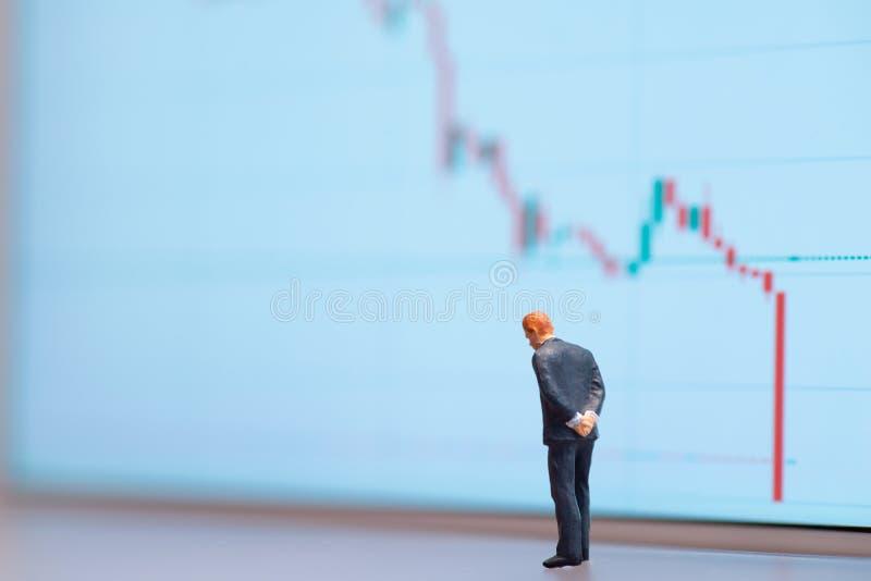 Homem de negócios em miniatura de foco seletivo que olha para baixo - queda do preço do petróleo bruto com gráfico descendente fo fotografia de stock royalty free