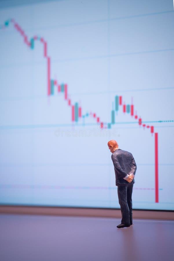 Homem de negócios em miniatura de foco seletivo que olha para baixo - queda do preço do petróleo bruto com gráfico descendente fo fotos de stock royalty free