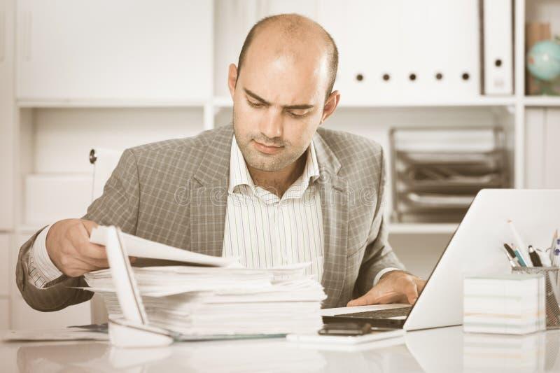 Homem de negócios em originais da visão da camisa na tabela foto de stock royalty free
