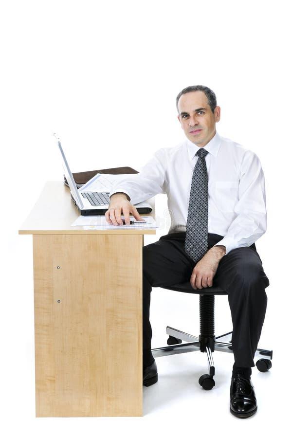 Homem de negócios em sua mesa no fundo branco imagem de stock royalty free