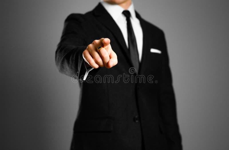 Homem de negócios em um terno preto, em uma camisa branca e em um laço apontando o fi foto de stock royalty free