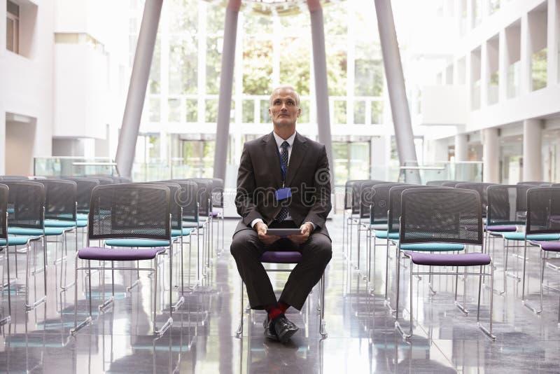 Homem de negócios In Empty Auditorium que prepara-se para fazer o discurso imagens de stock