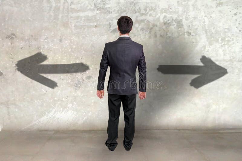 Homem de negócios entre duas escolhas diferentes fotografia de stock royalty free