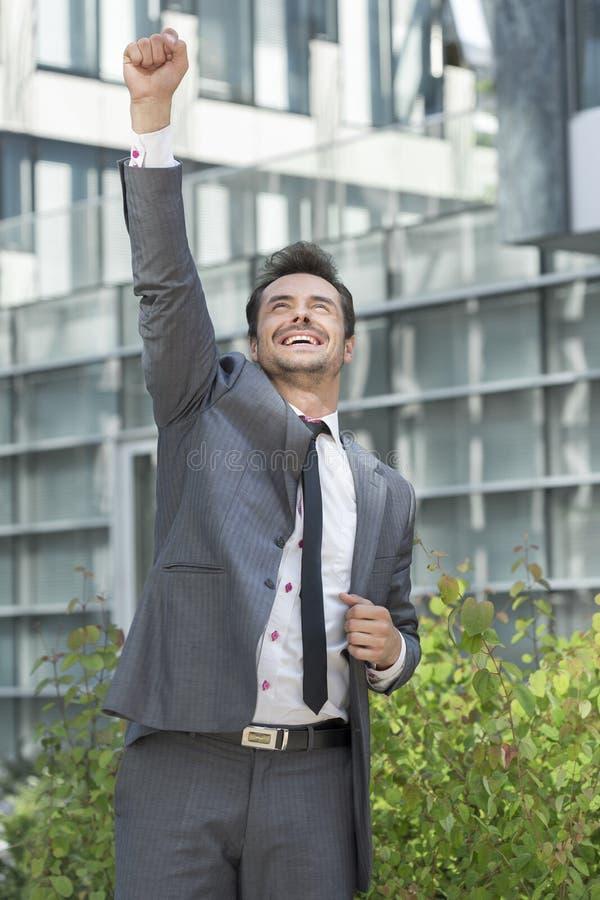 Homem de negócios entusiasmado que comemora o sucesso fora do prédio de escritórios imagem de stock