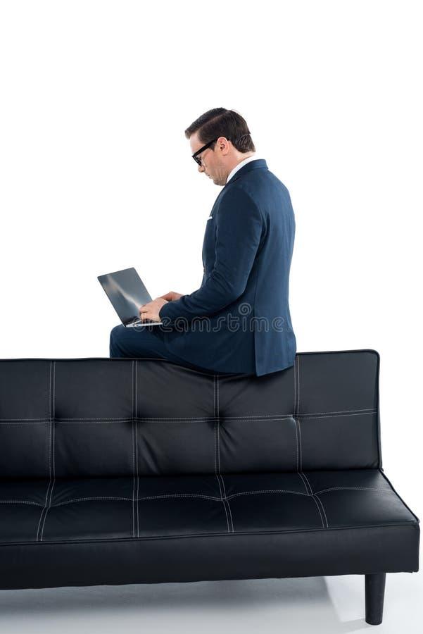 homem de negócios envelhecido médio que senta-se no sofá e que usa o portátil foto de stock royalty free
