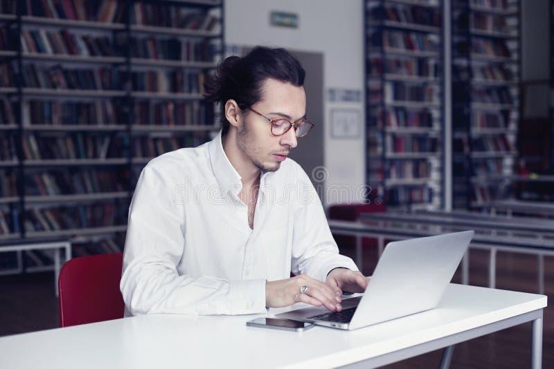 Homem de negócios, escrita da estudante universitário e funcionamento no portátil, em um co-trabalho ou em uma biblioteca pública foto de stock royalty free