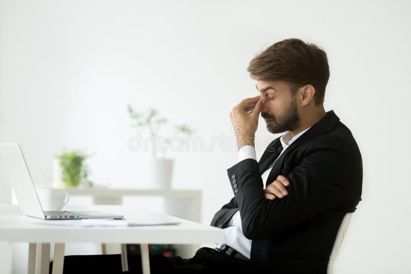 Homem de negócios esgotado que sente cansado fazendo massagens a ponte do nariz imagem de stock royalty free