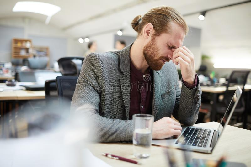 Homem de negócios esgotado Working no escritório do espaço aberto imagens de stock royalty free