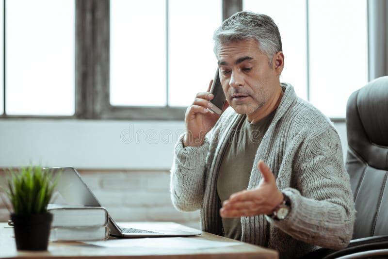 Homem de negócios esperto agradável que fala com seu sócio foto de stock royalty free