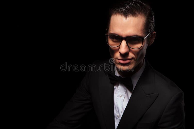 Homem de negócios esperto no terno preto que levanta no estúdio escuro imagens de stock