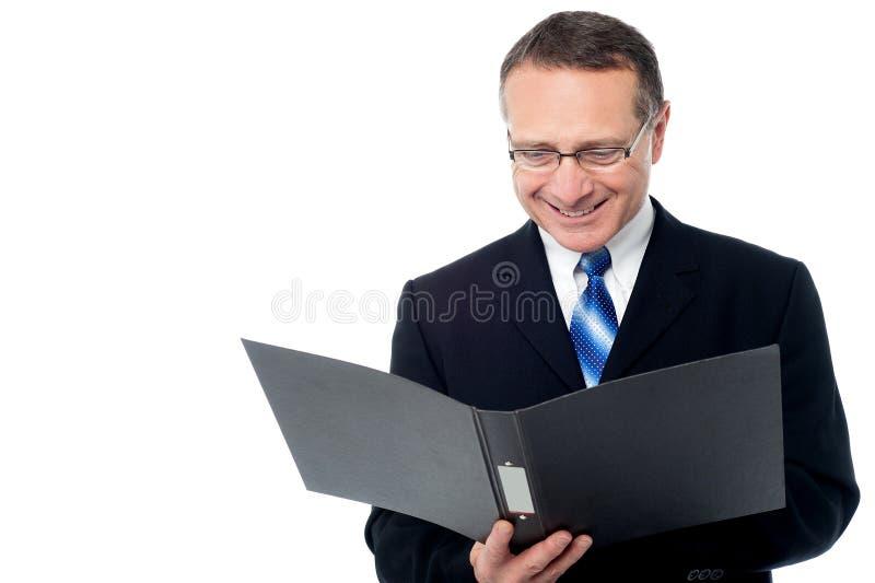 Homem de negócios esperto que guarda um arquivo aberto foto de stock royalty free