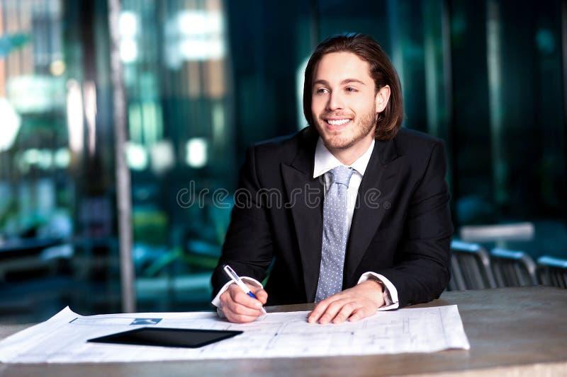 Homem de negócios esperto que projeta seus planos fotografia de stock royalty free