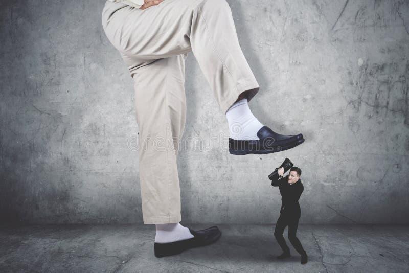 Homem de negócios estarrecente que cobre sua cara que está sendo atacada por uns pés gigantes foto de stock royalty free