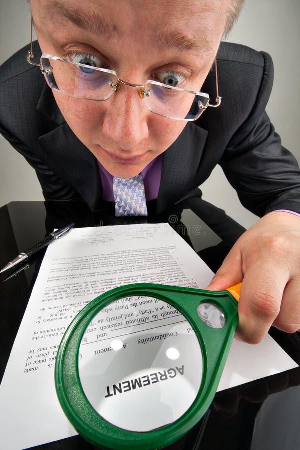 Homem de negócios estranho que examina o acordo fotos de stock royalty free