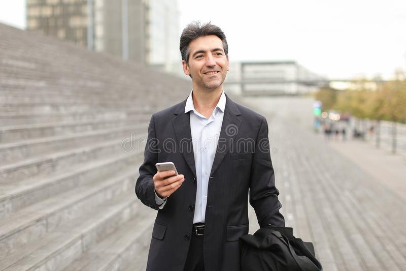 Homem de negócios europeu que anda e que fala pelo telefone imagem de stock
