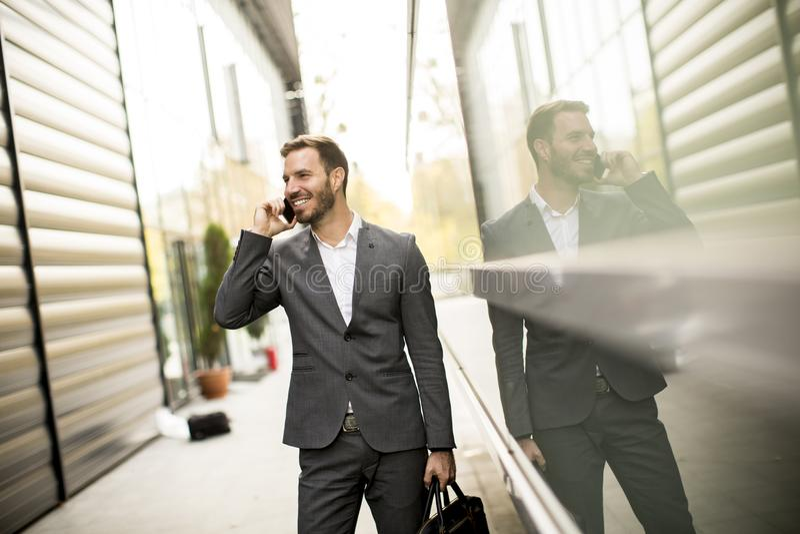 Homem de negócios executivo do homem bem sucedido novo que usa seu cel móvel fotos de stock