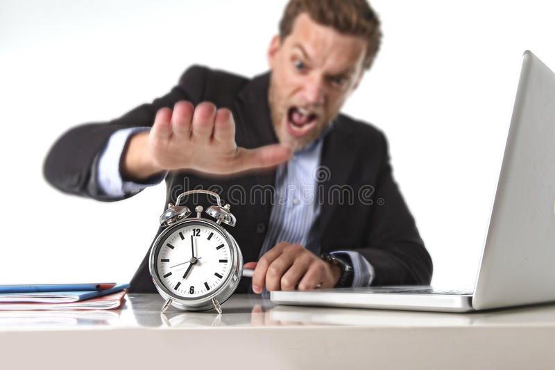 Homem de negócios explorado na mesa de escritório forçada e frustrada com despertador dentro fora do conceito do tempo e do fim d fotografia de stock