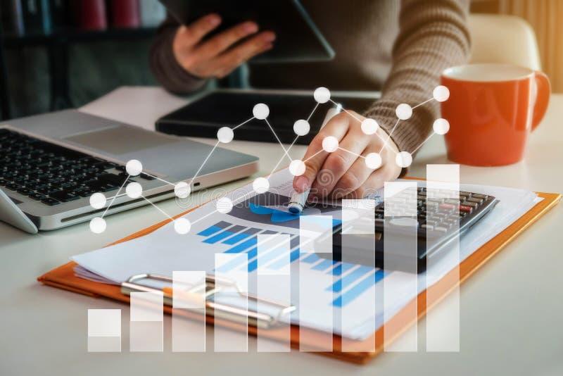Homem de negócios fêmea que trabalha no escritório da mesa com utilização de uma calculadora para calcular fotografia de stock royalty free