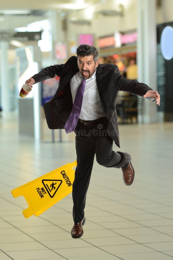 Homem de negócios Falling de Hispanoc no assoalho molhado fotografia de stock