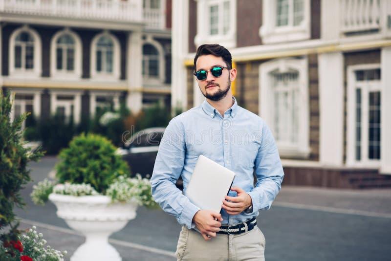 Homem de negócios farpado à moda nos óculos de sol que anda em torno do quarto britânico Guarda o portátil, olha seriamente fotos de stock royalty free