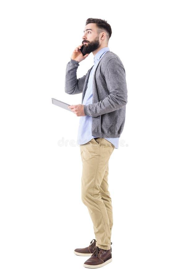 Homem de negócios farpado à moda novo ocupado no telefone que guarda a tabuleta e que olha acima fotos de stock royalty free
